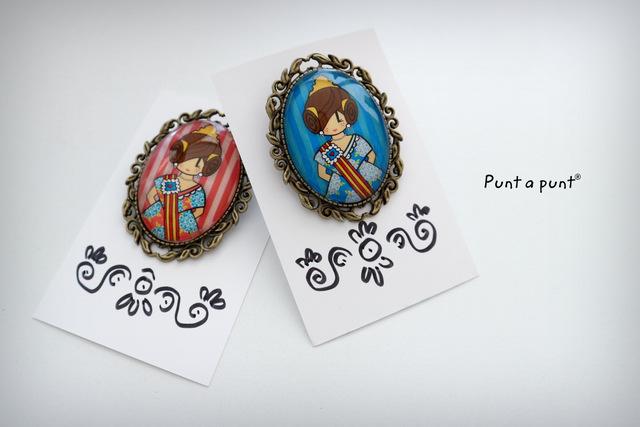 Broches de aleación de metales en acabado bronce con el diseño original de Punt a punt® de Pepetta Fallera. Ideales para presumir en el blusón, la banda, la chaqueta polar o el bolso o mochila.